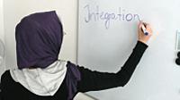 Kobieta w chustce pisze na tablicy.
